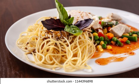 Italian pasta Spaghetti with vegetables and chicken. With red salsa sauce and basil. It is on the table in the restaurant. Copy space, selective focus
