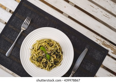 Italian pasta with spinach, pesto, mushrooms and parmesan top view