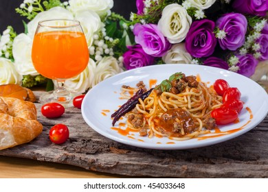 Italian pasta in tomato sauce, decorated with tomatoes and bread and orange juice on a wooden table.