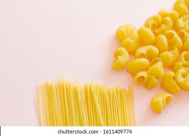 Italian pasta. Yellow long spaghetti and pasta on pink background. Raw spaghetti Bolognese. Raw spaghetti. The concept of food. Concept of Italian cuisine and menu. Flat lay. Macaroni durum varieties.