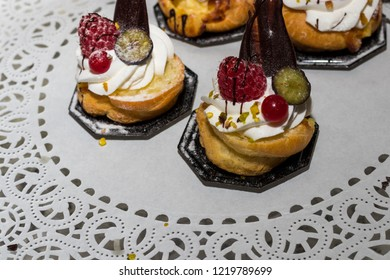 Italian pastry on the table with sweets with chocolate, cream, pistachio, strawberry and other sweet ingredients.