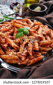 italian penne arrabiata on a clay plate with fresh basil and grated goat cheese on a rustic table with brown cloth, vertical view from above