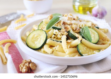 Italian penne pasta with roasted zucchini ang garlic, grated parmesan cheese and walnuts on light background