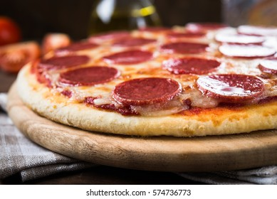 Italian Pepperoni pizza with salami on dark wooden background close up. Italian traditional food. Popular street food.