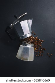 Italian percolator and coffee beans on dark background