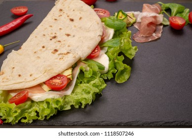 Italian piadina romagnola flatbread with lettuce, cherry tomatoes, prosciutto ham, mozzarella cheese and grilled zucchini