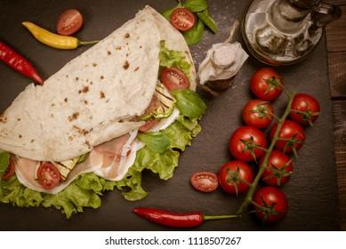 Italian piadina romagnola flatbread with lettuce, cherry tomatoes, prosciutto ham, mozzarella cheese and grilled zucchini. Vintage effect