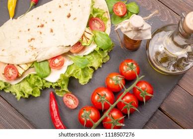 Italian piadina romagnola flatbread with lettuce, cherry tomatoes, prosciutto ham, mozzarella cheese and grilled zucchini. Top view