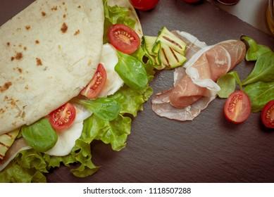 Italian piadina romagnola flatbread with lettuce, cherry tomatoes, prosciutto ham, mozzarella cheese and grilled zucchini with vintage effect