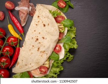 Italian piadina romagnola flatbread with lettuce, cherry tomatoes, prosciutto ham, mozzarella cheese and grilled zucchini. Top view and copy space