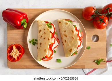 Italian piadina romagnola flatbread with red pepper, tomatoes, prosciutto ham, cheese and basil on the plate on white wooden background. Italian restaurant cuisine. Top view, copy space for text