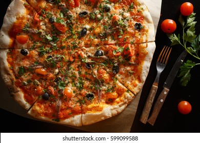 Italian pizza with anchovies, olives and tomatoes, on the table. Italian Cuisine.