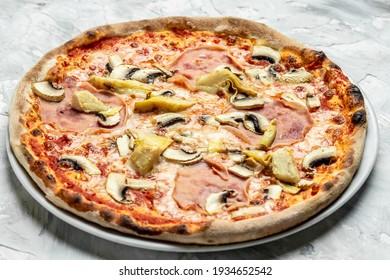 Italian pizza capriciosa mushroom artichokes, tomato and mozzarella cheese. Food recipe background. Close up.