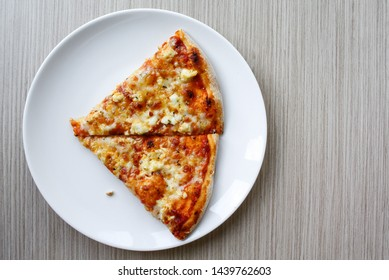 Italian pizza four cheese on white dish at wooden table background