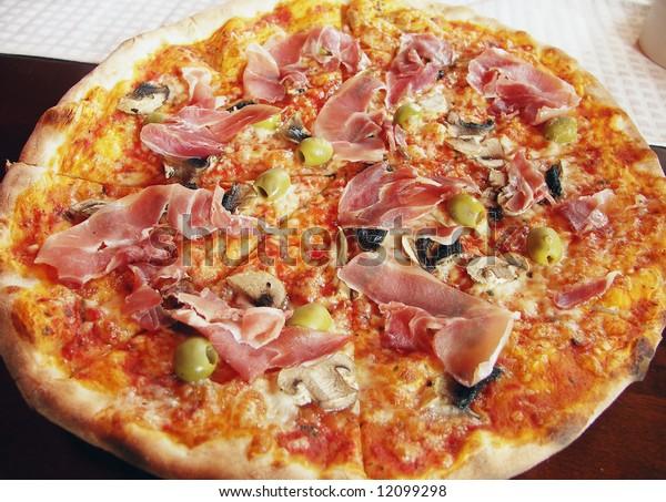 Italian pizza with italian ham, olives and field garlic.