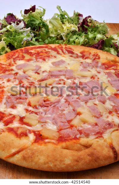 italian pizza with ham, salami and salad