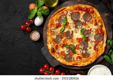 Italian pizza on a wooden serving board on a black background with mushrooms, mozzarella, sausage, parmesan, tomatoes and basil on the table.  Top view
