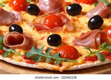 Italian pizza with prosciutto ham, tomatoes, black olives and arugula macro horizontal