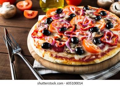 Italian pizza with salami, mushroom, tomatoes, sweet pepper, black olives and purple onion on dark wooden background close up. Italian traditional food. Popular street food.