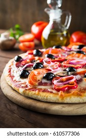 Italian pizza with salami, mushroom, tomatoes, sweet pepper, black olives and purple onion on dark wooden background close up. Italian traditional food. Popular street food.