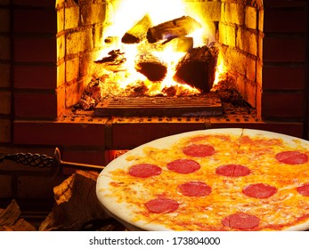 italian pizza with salami and open fire in wood burning oven