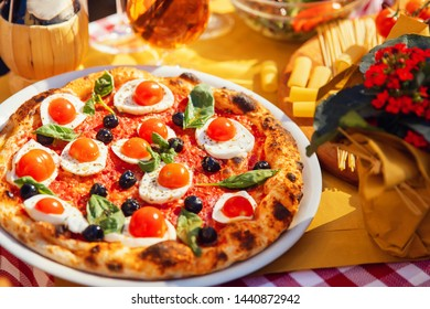 Italian pizza with tomatoes, mozzarella cheese, basil, black olives on board. Concept restaurant.