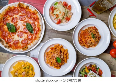 Italian pizzas and salads top view. Pepperoni, greek salad, salad caesar, pasta bolognese.