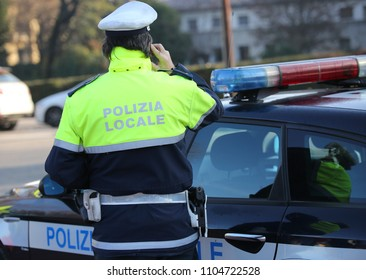 Italian policeman with the  text POLIZIA LOCALE that means local police in Italian language uses the cell phone during an emergency call and the police car