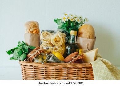Italian products. Italian traditions. Ingredients. Healthy food. Basket with products. Basket with a gift. Food delivery. A food set. White wooden table.