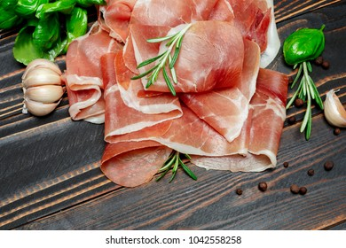Italian prosciutto crudo or spanish jamon. Raw ham on wooden background