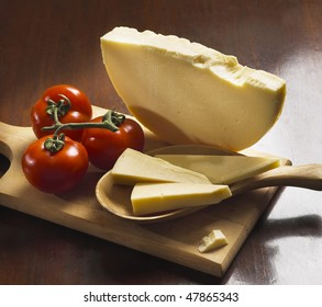 Italian provolone and tomatoes on wooden board