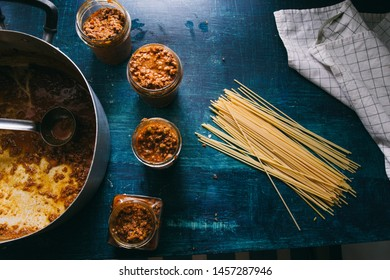Italian ragu, meat sauce, and raw spaghetti, freshly made italian bolognese sauce, poured inside glass container ready to be stocked for winter, with fresh raw spaghetti on a blue background, top view