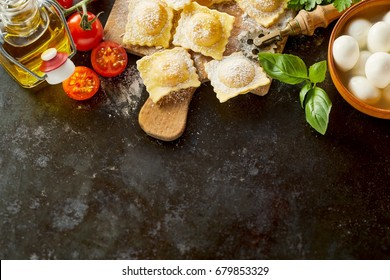 Italian ravioli border with ingredients with freshly made uncooked savory pasta, tomatoes, mushrooms, olive oil and basil on a textured dark surface with copy space