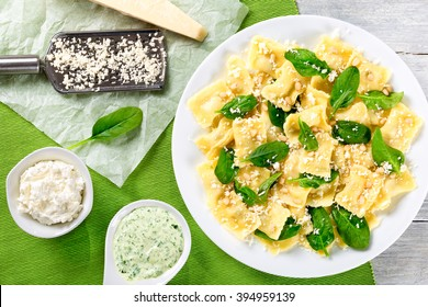 italian ravioli filled with ricotta and spinach decorated with green leaves, grated parmesan cheese and pine nuts on a white dish, creamy sauce in a gravy boat, top view, close-up