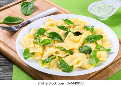 italian ravioli filling with ricotta cheese and spinach decorated with green leaves on a white dish, creamy sauce in a gravy boat on a cutting board. healthy and easy recipe, close-up