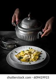 Italian ravioli in the plate on the dark background