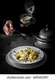 Italian ravioli in the white plate on the dark backgrond