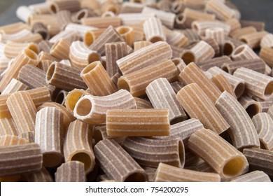 Italian raw colored whole wheat pasta on black background