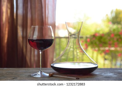 Italian red wine in goblet with decanter on natural background