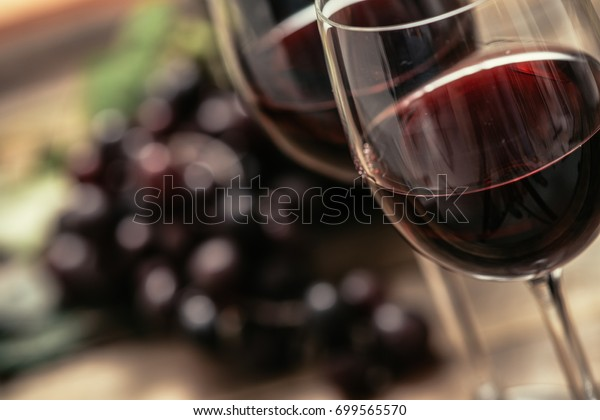 Italian red wine tasting and wine culture: wine glass and grape on a rustic wooden table
