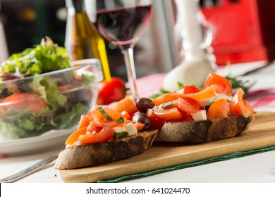 Italian restaurant freshly served bruschetta with cheese, tomato, olives and wine and salad in background