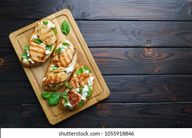 Italian restaurant menu, food background. Appetizing bruschetta with grilled chicken, ricotta and basil flat lay on wooden table with free space