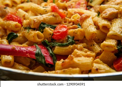Italian rigatoni pasta chicken vegetable alfredo with sliced cherry tomatoes in serving pot
