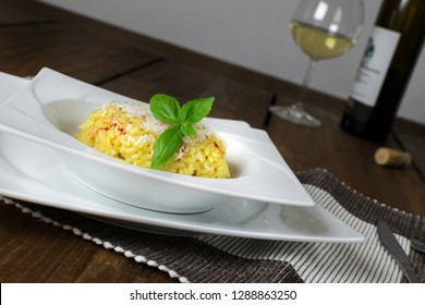 Italian risotto alla milanese with saffron. Served in white plate on wooden table.