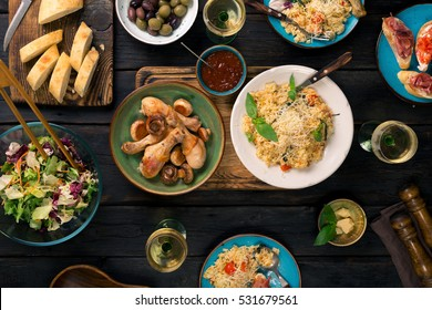 Italian risotto with cherry tomatoes, basil and parmesan cheese, roasted chicken legs, snacks and wine on dark wooden table. Italian food table, top view