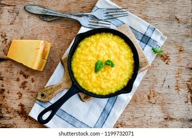 Italian risotto milanese  with parmesan cheese and fresh basil on rustic background