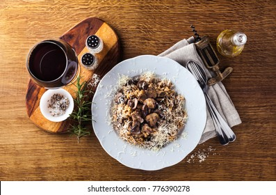 Italian risotto with mushrooms and Parmesan cheese in a plate on a wooden table. a glass of red wine and olive oil.