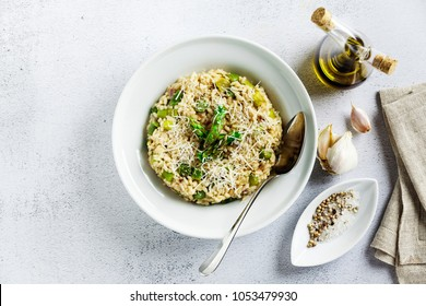 Italian risotto with spring fresh asparagus and parmesan cheese in a plate and ingredients on a stone white table
