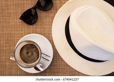 Italian Riviera tourism gear. Café Creme, glasses, and a straw hat.