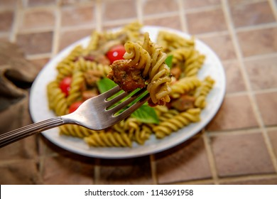 Italian rotini spiral pasta in nutty basil pesto sauce with grape tomatoes sausage kidney beans and mushrooms